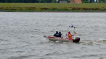 Taucher der Bereitschaftspolizei suchen auf der Elbe bei Winsen-Drage (Niedersachsen) nach der Familie.