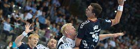 Flensburgs Rasmus Lauge Schmidt (r.) wirft den Ball gegen Kiels Patrick Wiencek.