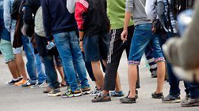 Flüchtlinge warten nach ihrer Ankunft in München auf Busse, die sie in Unterkünfte bringen.