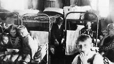 September 1945. Flüchtlinge drängen sich auf dem beengten Platz in einer Notunterkunft des Lagers Friedland bei Göttingen.