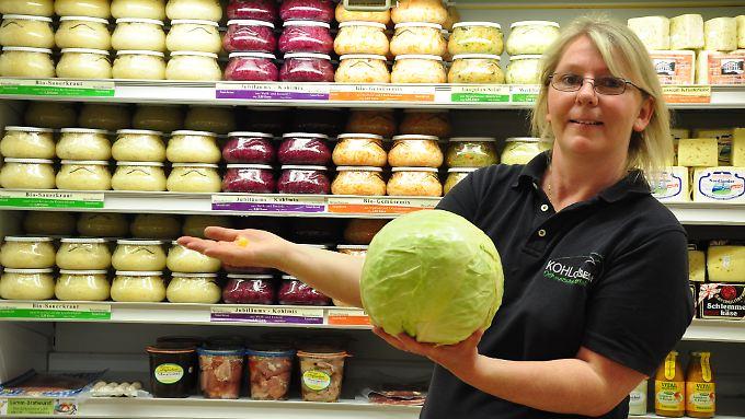 Größenvergleich: Susanne Schröder-Manusch mit einem Suurkruut Bonsche (Genau hinsehen!) und einem Weißkohl für Sauerkraut.