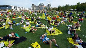 Dutzende Läufer liegen erschöpft vor dem Reichstag.