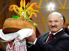 Der weißrussische Diktator hält einen prächtigen Laib Brot.
