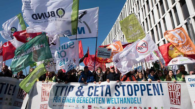 """Demonstranten laufen in Berlin mit einem """"TTIP & CETA STOPPEN!""""-Transparent durch die Straßen."""