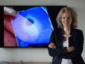 Bettina Lotsch vor einer Projektion, auf der eine Abbildung eines Prototyps eines Feuchtesensors zu sehen ist.