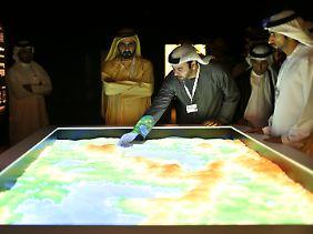Minister der Vereinigten Arabischen Emirate beraten sich über einer Weltkarte aus Sand.