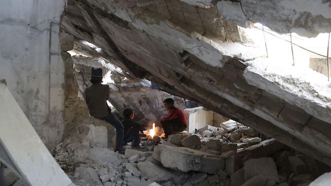 In der Ruine eines zerstörten Gebäudes im syrischen Maaret al-Numan wärmen sich Jungs am Feuer.