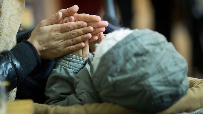 Eine Mutter versucht in einem Wartezelt vorm Lageso, ihr Kind mit den Händen zu wärmen.
