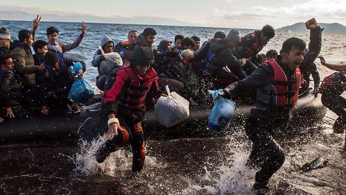 Migranten jubeln nach erfolgreicher Ankunft auf der griechischen Insel Lesbos.