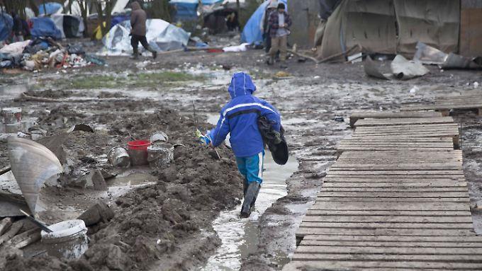 Ein Kind watet durch den Matsch in einem Flüchtlingslager in Frankreich.