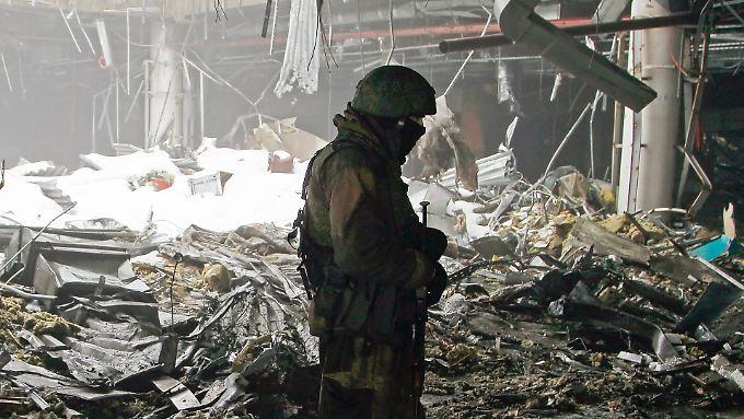 Ein pro-russischer Separatist patrouilliert am stark beschädigten Flughafen der ostukrainischen Metropole Donetzk.