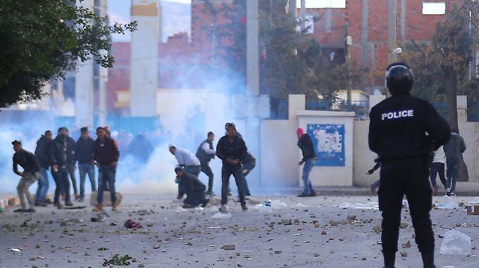 Demonstranten werfen in Tunis mit Steinen auf Polizisten: Die Unruhen haben das gesamte Land erfasst.