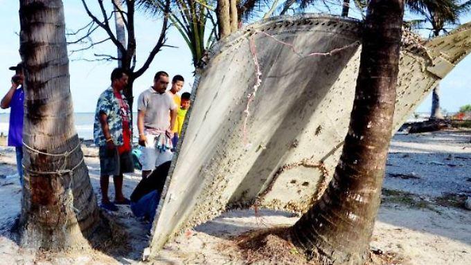 Fischer begutachten das Wrackteil an seinem Fundort an einem Strand in Südthailand.