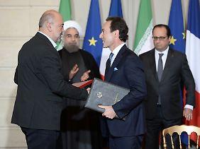 Handschlag nach der Unterzeichnung: Airbus-Chef Fabrice Bregier (r.) freut sich mit dem Chef der iranischen Luftfahrtbehörde (CAO), Ali Abedzadeh.