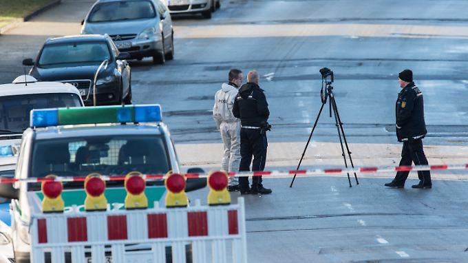 Kriminalbeamte der Spurensicherung untersuchen den Tatort vor der Flüchtlingsunterkunft.