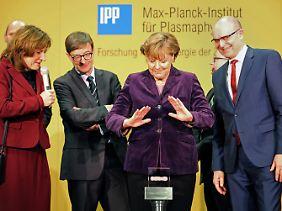 Kanzlerin Angela Merkel drückt den Startknopf für die erstmalige Erzeugung von Wasserstoff-Plasma.