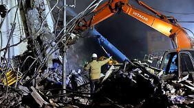 Mit schwerem Gerät versuchen die Bergungskräfte Überlebende aus den Trümmen zu retten.