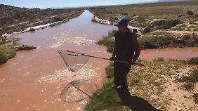 Bauer Juan Iquina fischt erfolglos im rotgefärbten Wasser.