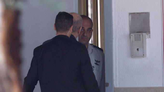 """Die Leibwächter kommen nur bis zur Gefängnispforte: Ehud Olmert (M.) """"wird (...) mit dem Moment des Haftantritts in unsere Sicherheitsverantwortung übergeben""""."""