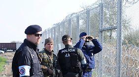 Gemeinsam patrouillieren ein tschechischer Polizist, ein slowakischer Polizist, ein ungarischer Soldat und ein ungarischer Polizist an der Grenze von Ungarn und Serbien.