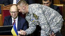 Ein demonstrativ in eine Uniform gekleideter Abgeordneter gratuliert Jazenjuk nach der Abstimmung.