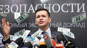 Bei der Vorstellung seines Berichts wird Jaschin mit falschen Dollarscheinen beworfen und beschimpft.