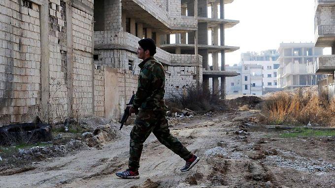Ein Soldat des Regimes läuft durch das von Bombenangriffen beschädigte südsyrische Daraja.