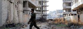 Ein Soldat des Regimes läuft durch einen durch Bombenangriffe beschädigten Straßenzug im südsyrischen Daraja.