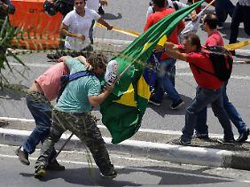 Kurz nach Beginn der Razzia gehen Unterstützer und Gegner bei spontanen Kundgebungen aufeinander los.