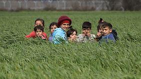 Flüchtlingskinder spielen nahe der griechisch-mazedonischen Grenze in einem Feld.