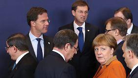 Die EU-Staats- und Regierungschefs, darunter Kanzlerin Angela Merkel, beraten über die Vorschläge des türkischen Premiers (l.).