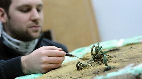Restaurator Jörg Stolz vom Bayerischen Landesamt für Denkmalpflege zeigt, wie dünne Kupferbarren aus dem Boden gelöst werden.