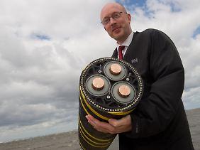 Strom aus der Ostsee: Landesverkehrsminister Christian Pegel mit einem der Seekabel, mit dem Netzbetreiber die Windräder ans Stromnetz anschließen wollen.
