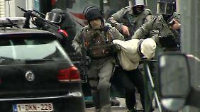Die belgischen Sicherheitskräfte führen einen Verdächtigen ab.
