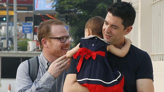 Gordon Lake (l.) und Manuel Santos mit Baby Carmen bei der Ankunft vor Gericht in Bangkok.
