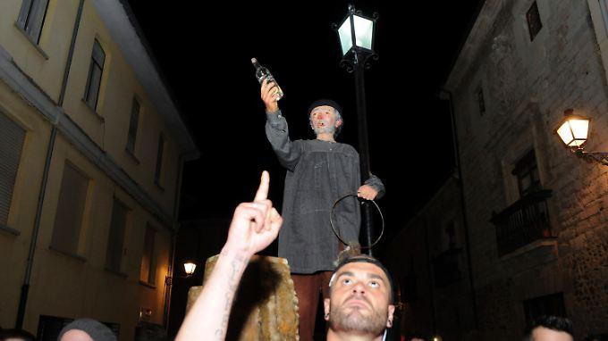 """Genarín mit der Schnapsflasche in der Hand: So wird der """"Volksheilige"""" durch die Straßen Leóns gezogen."""