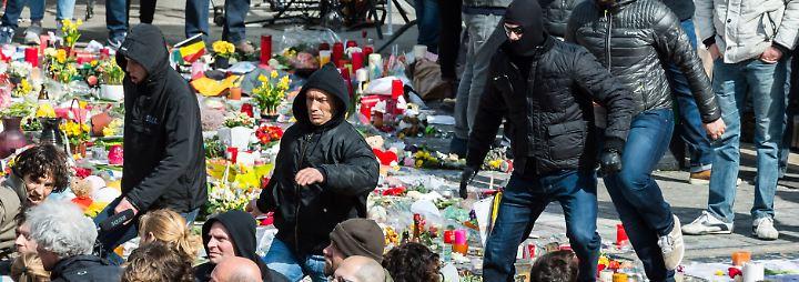 Die rechten Demonstranten laufen über Blumen und andere Gegenstände, die am Place de la Bourse in Gedenken an die Opfer niedergelegt wurden.