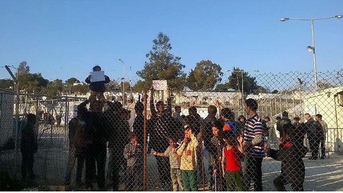 Im Lager internierte Menschen stehen am Zaun und protestieren gegen die Bedingungen.