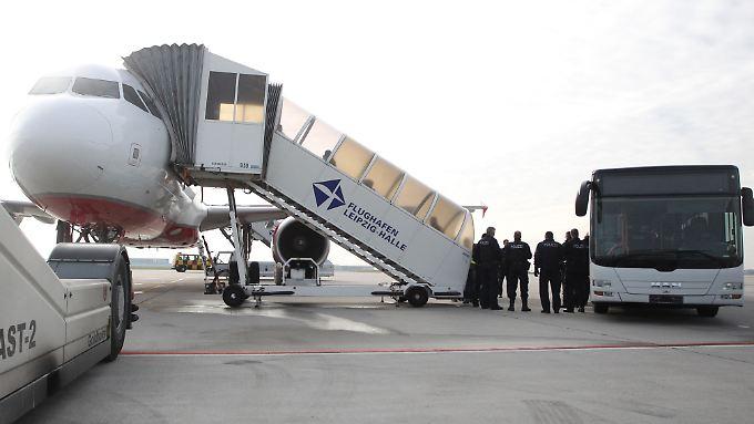 Polizisten überwachen die Ankunft abgelehnter Asylbewerber auf dem Flughafen Leipzig-Halle.
