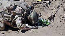 Ein Soldat betet an einem Massengrab für die Opfer des Speicher-Massakers.