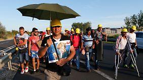 """""""Marsch der Hoffnung"""": Vorneweg läuft ein Mann mit einem Merkel-Bild."""
