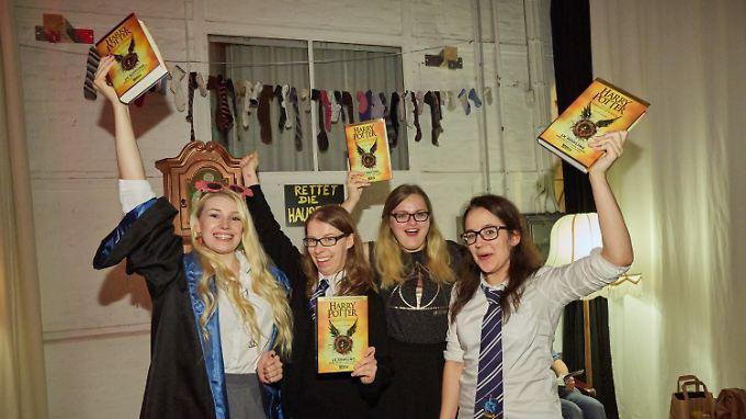"""Nun auch auf Deutsch: Fans jubeln mit ihren druckfrischen Exemplaren von """"Harry Potter und das verwunschene Kind""""."""