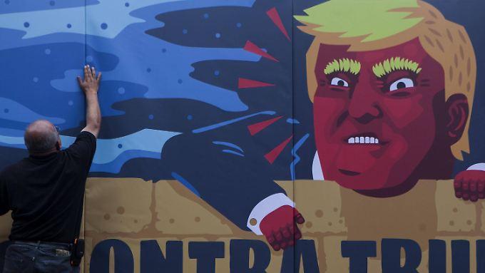 Ein Graffito mexikanischer Demonstranten zeigt Donald Trump, der über die von ihm angestrebte Mauer nach Mexiko blickt.
