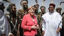 Bundeskanzlerin Merkel wird im Niger von Präsident Issoufou sowie Männern vom Stamm der Wodaabe begrüßt.