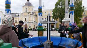 Gläubige füllen das heilige Quellwasser im Kloster von Sergijew Possad ab.