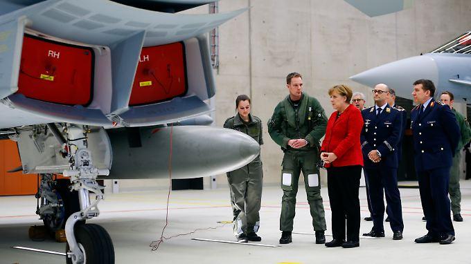 Kanzlerin Angela Merkel begutachtet Eurofighter, von denen Berichten zufolge derzeit nur jeder dritte einsatzbereit ist. Geht es nach der Nato, gibt Deutschland wie die meisten EU-Staaten zu wenig für Verteidigung aus.