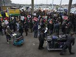 Reisende passieren am New Yorker Flughafen John F. Kennedy Demonstranten, die gegen den Einreisestopp protestieren.