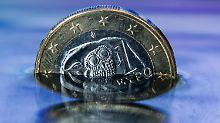 """ARCHIV - ILLUSTRATION - Eine griechische Euro-Münze steht am 22.06.2015 in Schwerin (Mecklenburg-Vorpommern) in einer Wasserfläche, in der sich die griechische Flagge spiegelt (gestelltes Foto). (zu dpa """"Euro-Finanzminister diskutieren über griechisches Sparprogramm"""" vom 26.01.2017) Foto: Jens Büttner/dpa-Zentralbild/dpa +++(c) dpa - Bildfunk+++"""