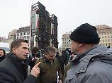 """Der Wirtschaftsminister und stellvertretender Ministerpräsident von Sachsen, Martin Dulig (SPD, l), spricht am 07.02.2017 auf dem Neumarkt in Dresden (Sachsen) vor der Skulptur """"Monument"""" des syrischen Künstlers Manaf Halbouni mit einem Demonstranten. Die Skulptur soll eine Brücke von Dresden nach Aleppo schlagen und wurde am gleichen Tag eingeweiht. Foto: Sebastian Kahnert/dpa-Zentralbild/dpa +++(c) dpa - Bildfunk+++"""