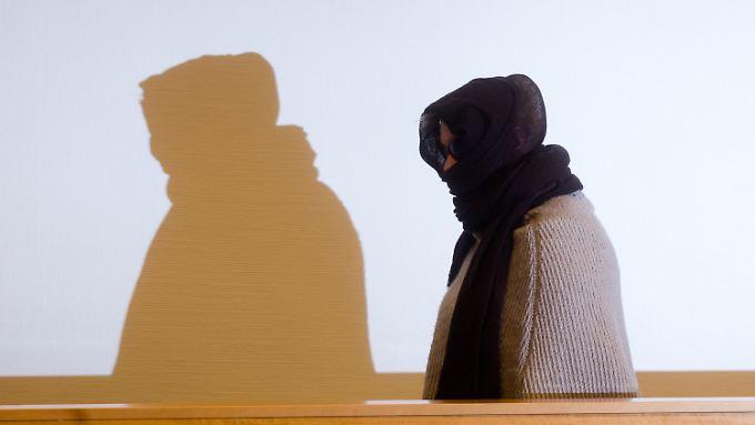 Die 22-jährige Laura S. tritt mit dunkler Sonnenbrille und einem braunen Schal um den Kopf in den Saal.